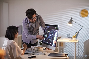 Employee pointing out risks on monitor
