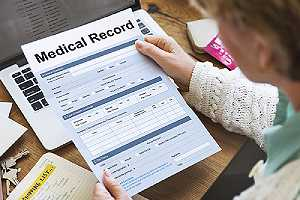 A healthcare provider checking a medical record report.One of the pros of Telehealth services saving time and money