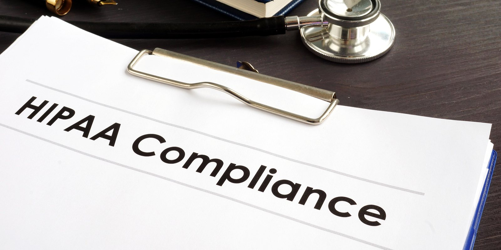 HIPAA Compliance documents with clipboard on a desk. HIPAA-compliant telehealth software improve internal workflow