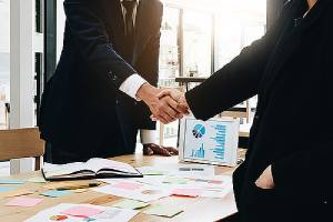 Business people shaking hands. Mergers and acquisitions often come with uncertainties
