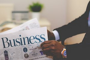 Businessman opening a newspaper. A closed market transaction is the opposite of an open market transaction