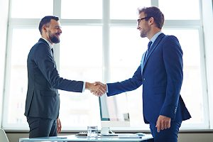 Client handshaking with a professional from a cybersecurity consulting firm