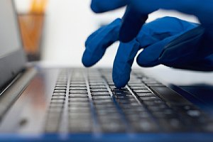 Hand in gloves typing on keyboard. Cybersecurity Risks concept