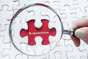 Magnifying glass over jigsaw puzzle. A merger or acquisition go through the process of due diligence