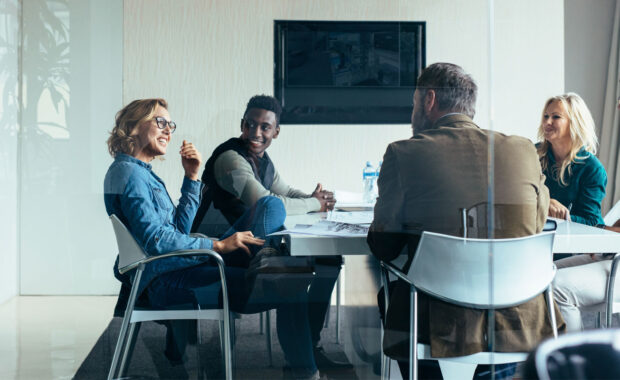 a group of executives discussing the benefits of hiring an outsourced CIO