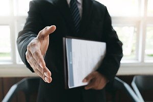 A job seeker extending his hand. Outsourcing to a third-party cybersecurity consulting firm is a cost-effective option