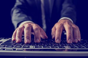 Closeup of a person typing on computer keyboard. Cybersecurity consulting firms have become a valuable resource