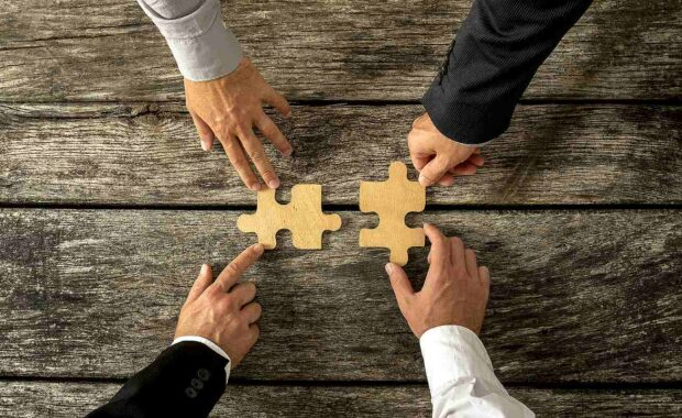 Group of business men joining two puzzle pieces. M&A integration planning concept