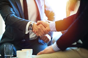 People shaking hands. Partnering with cybersecurity consulting firm can protect businesses