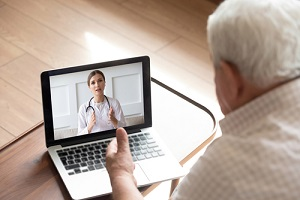 close up older man talking with doctor by video call
