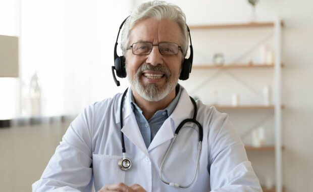 smiling senior old doctor wears headset looking at camera