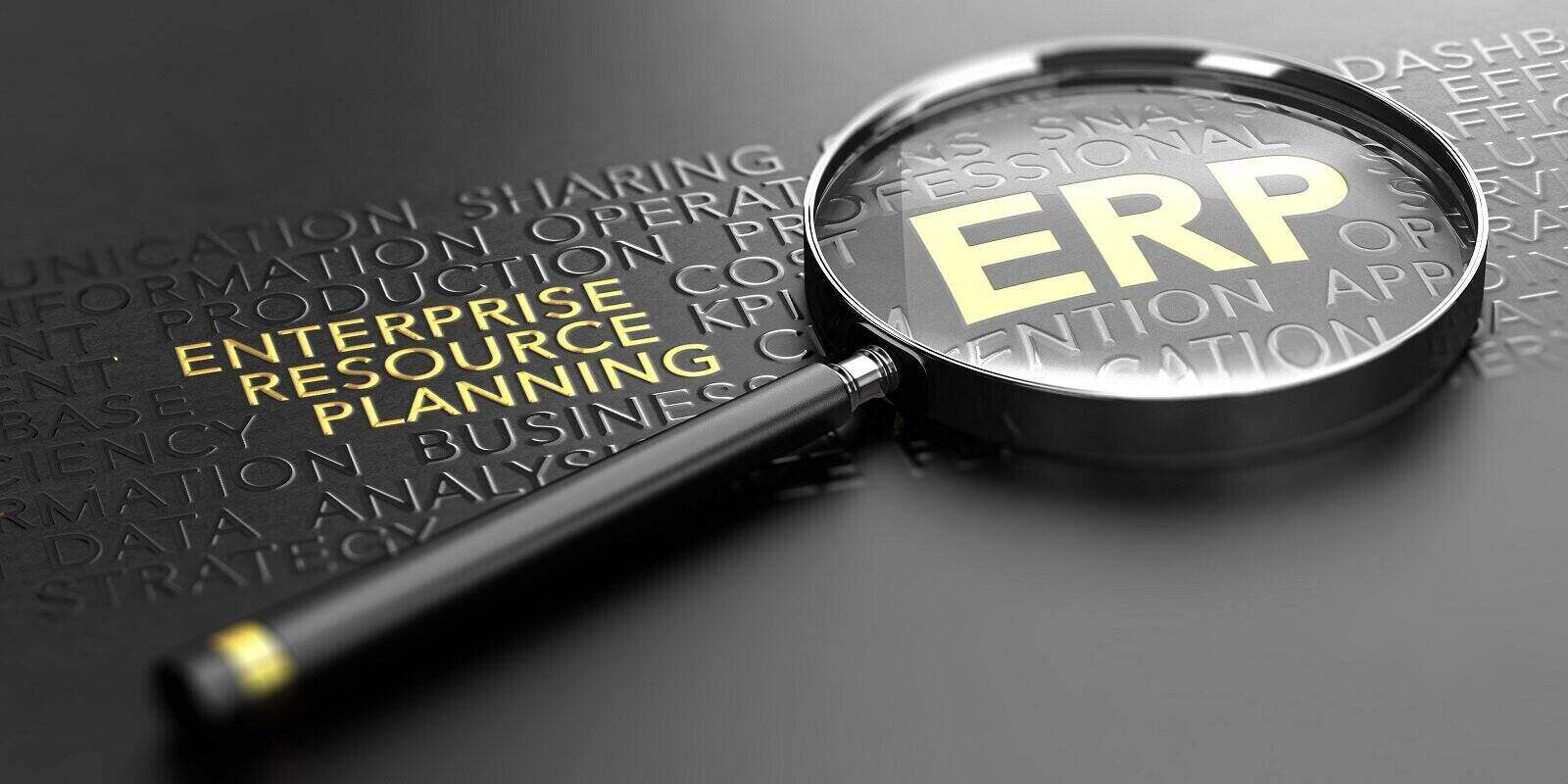 magnifying glass over black background and focus on the golden acronym erp