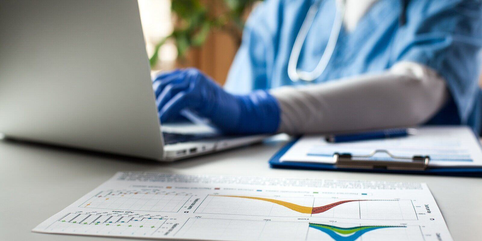 doctor working on laptop computer analyzing graphs charts